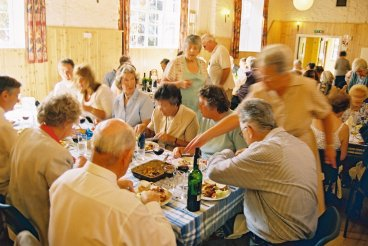 Picture of volunteers, supporters and listeners enjoying their food at the 2006 summer fundraising lunch, Biddenham village hall, north Bedfordshire