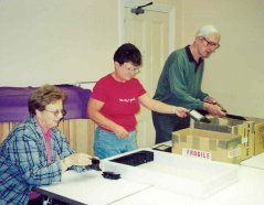 A photograph of three volunteers sorting returned tapes in the studio