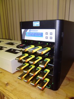 Photo of a black metal copier with 16 USB memory sticks plugged into the front.  Part of an audio tape duplicator is also shown behind left