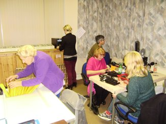 Photo of five volunteers - duplicating, checking and packing news programme wallets, photographed on 24th November 2011