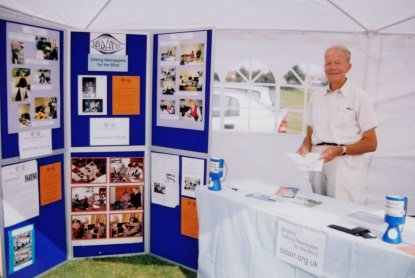 The late Dennis Craddock promoting Bedford and District Audio News at the Clapham village show.  Photo shows Dennis standing behind a table, with display boards to the left