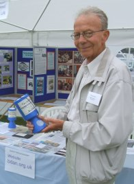 Portrait photograph of the late Dennis Craddock holding a collecting tin in front of a BDAN stall in 2007