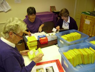Three preparers / sorters pictured in the studio with the main register list and piles of yellow wallets on 25th October 2011