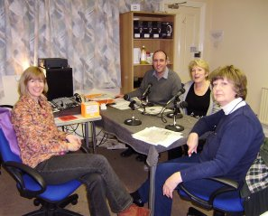 A team of four pictured after a weekly tape recording with the new desk, and curtains hung behind