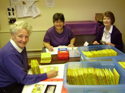 An image showing three smiling volunteers sitting at a table in the studio, checking returned tapes and USB memory sticks against the master register of listeners
