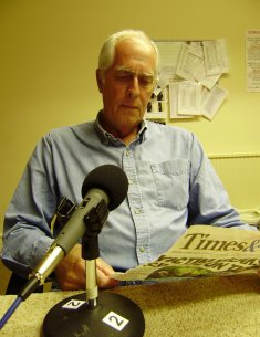 2011 photo showing a BDAN volunteer reading a newspaper page to tape via a microphone