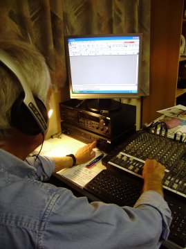 A male recordist, wearing headphones, operates the mixer and CD player whilst looking at a computer monitor.  Image taken from behind his shoulder