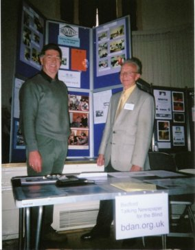 An image showing two BDAN volunteers standing behind a small table with BDAN display boards behind
