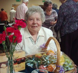 A photograph of listener, Vera Rust, with her raffle prize winnings - a basket of fruit and a box of chocolates.  Other event attendees are pictured behind, with pink carnations in the foreground
